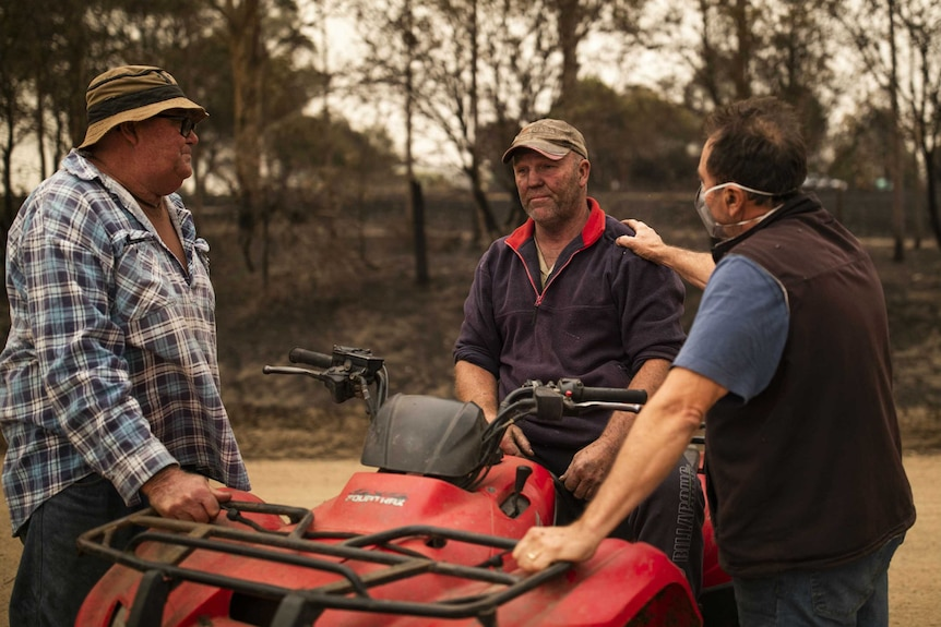 A farmer Steve Shipten with soot on his face is consoled by fellow farmers