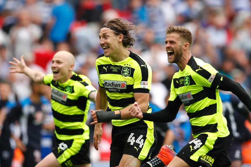 Huddersfield Town's Aaron Mooy, Michael Hefele and Martin Cranie celebrate after winning the Championship Play-Off Final.