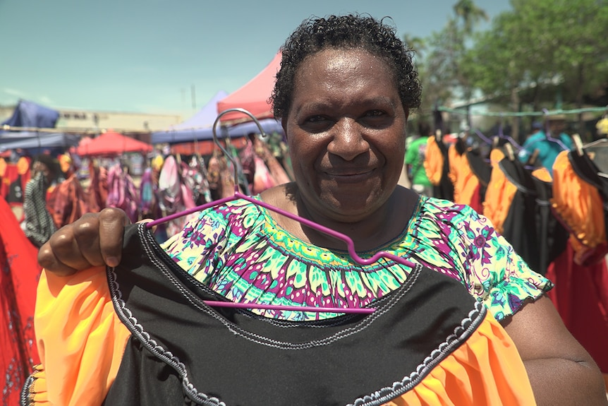 Market vendor Regina Robert with meri blouses she has made in PNG's flag colours.