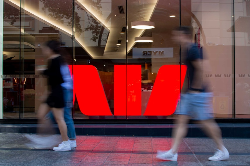 People walking past a Westpac sign.