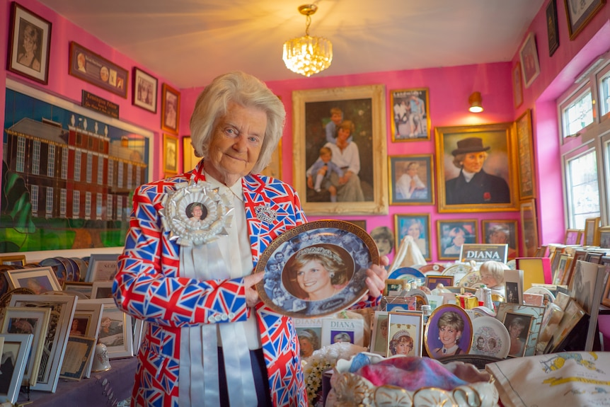 A woman in a Union Jack flag jacket holds a Princess Diana plate in a bright pink room.