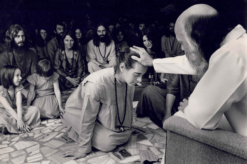A man with a long beard places a hand on the head of a kneeling woman while adults and children sit on the floor around them