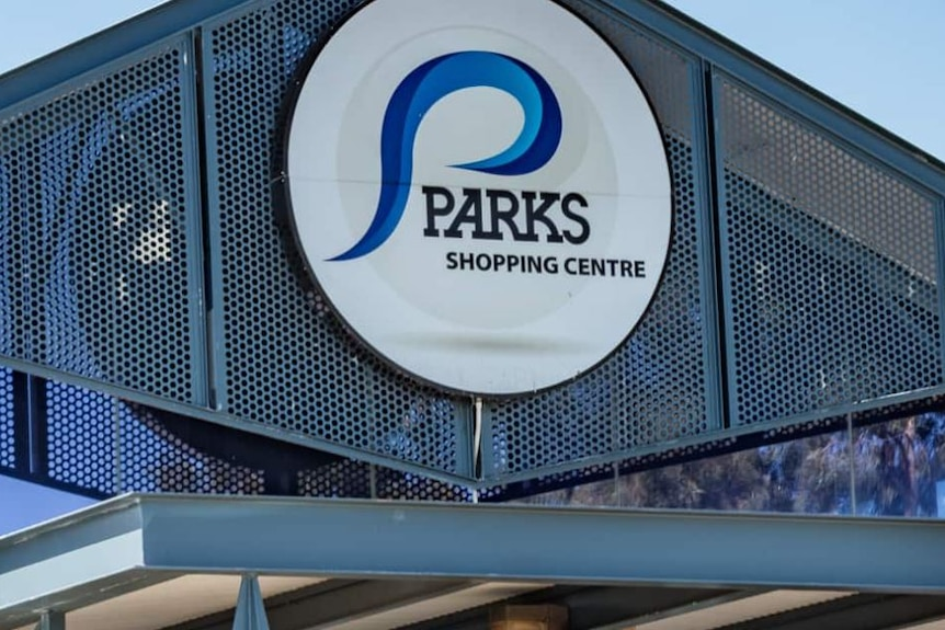 A sign on the top of a building saying Parks Shopping Centre