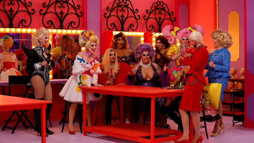 A group of drag queens huddled together around a table, the cast of RuPaul's Drag Race Down Under in episode 1