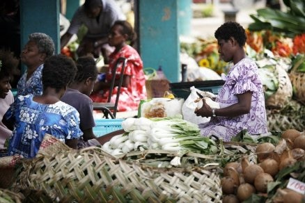 Women shop for fresh food at a street market.
