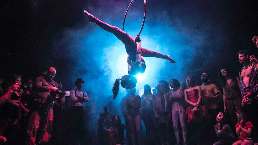 An acrobat handing from a ring with purple lighting