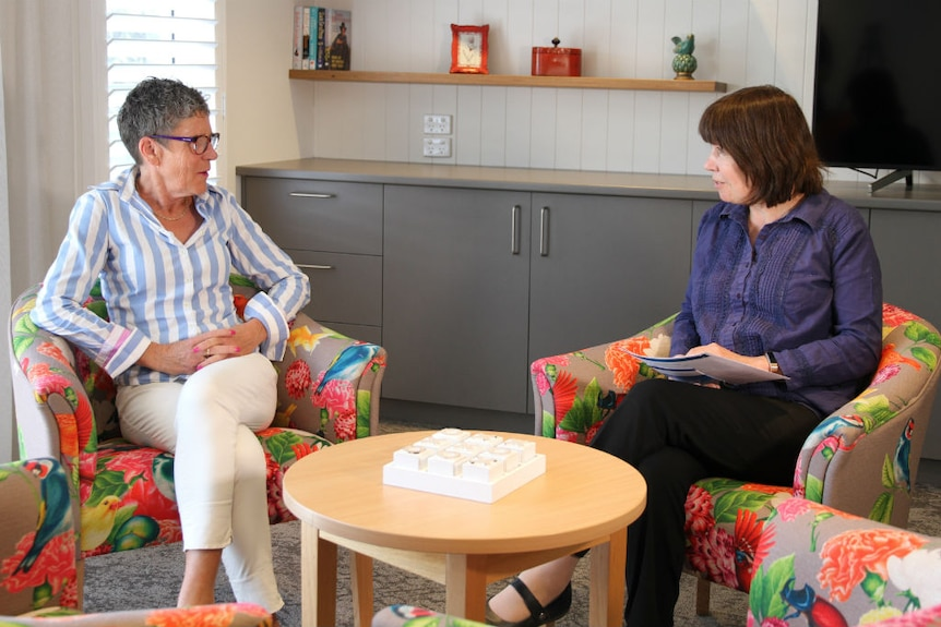 A woman with short grey hair and a woman with medium-length grey hair sitting in armchairs talking.