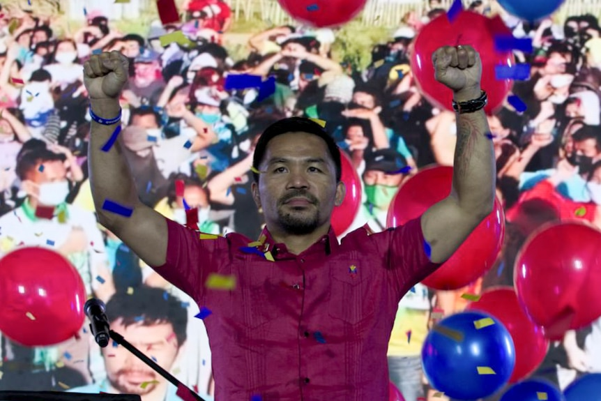 Manny Pacquiao raises his arms triumphantly during a national convention of his party, September 19, 2021.