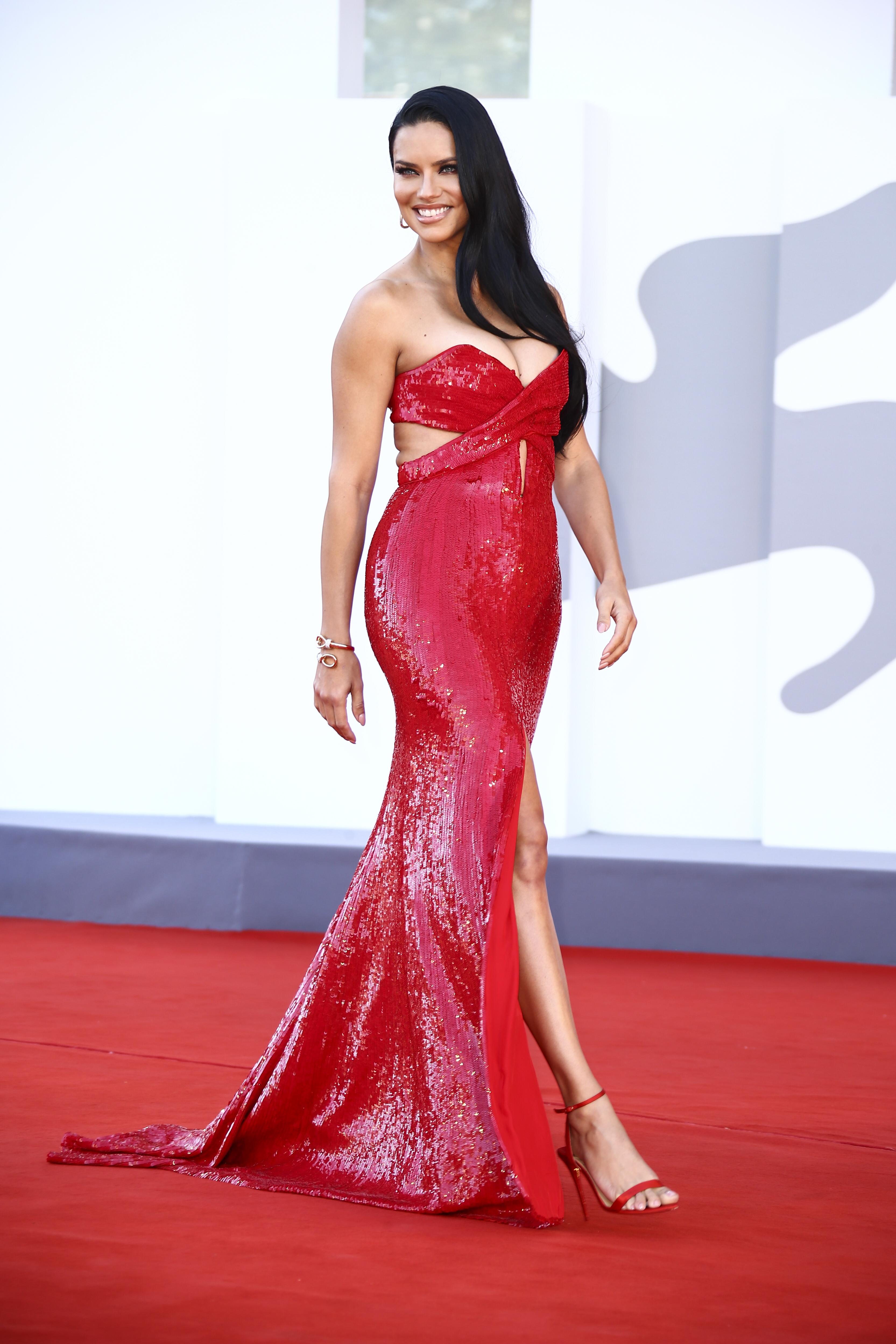 Adriana Lima indossa un maxi abito rosso scintillante con un lungo spacco.  C'è un taglio del corpetto del vestito.