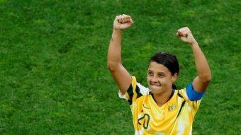A woman wearing a Matildas soccer team jersey holds her fists above her head.