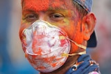 A man covered in colourful dye while wearing a medical face mask