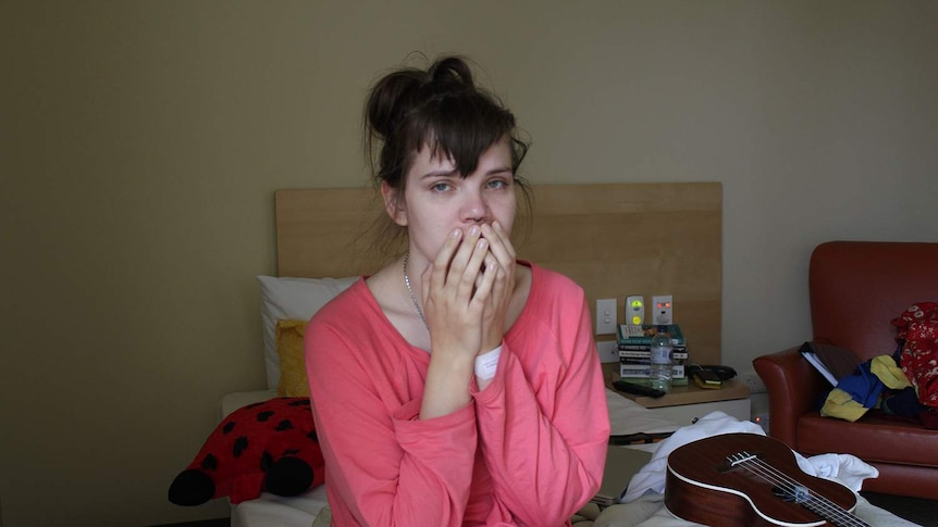 A young woman sitting on a hospital bed in pink pyjamas with her hands over her mouth and a resigned look on her face.