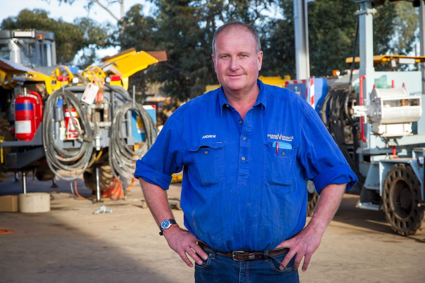 A mid-shot of Perseverance Drilling managing director Andrew Smith posing for a photo in front of drilling equipment.