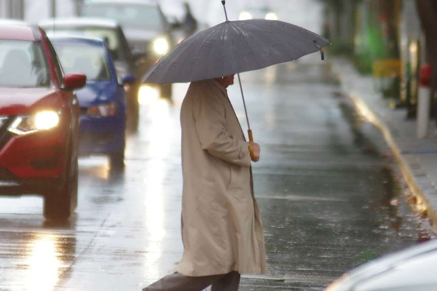 A man carrying an umbrella crosses a street in front of cars on a rainy day.