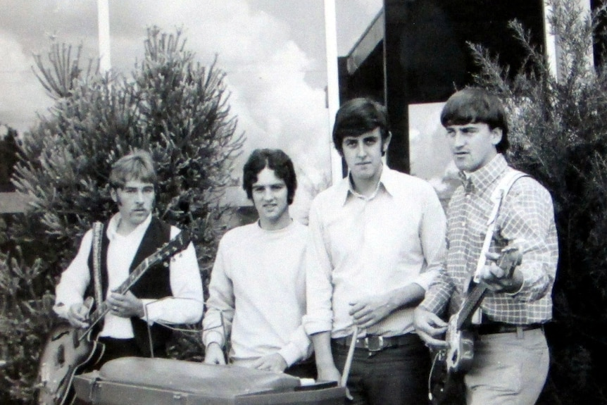 black and white photo of four men standing side by side holding instruments