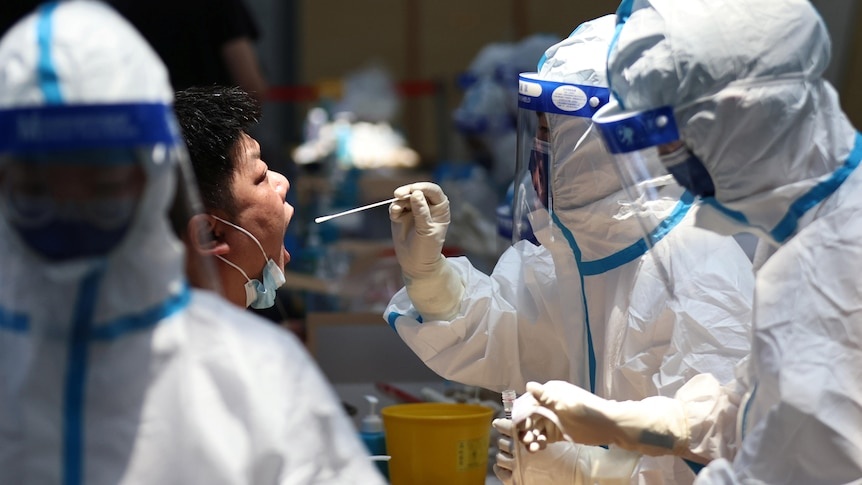 A man opens his mouth while a health worker in full PPE holds a swab in front of his face
