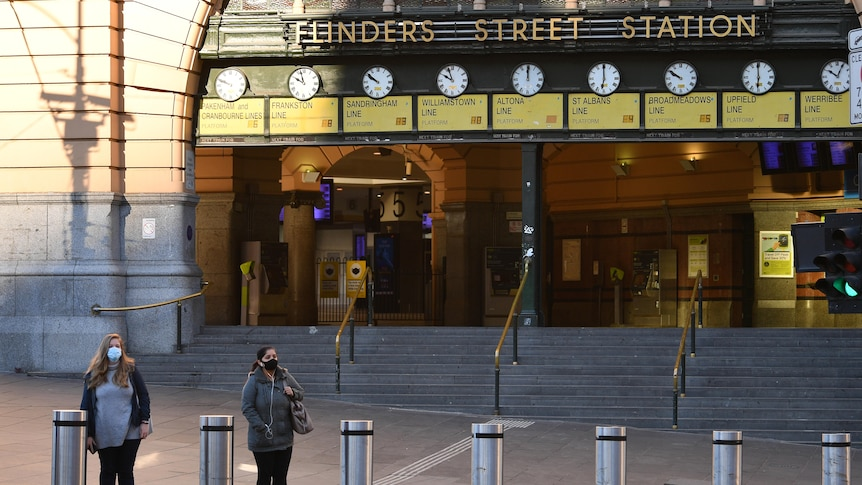 Two people wearing face masks wait on the street outside a quiet Flinders Street Station