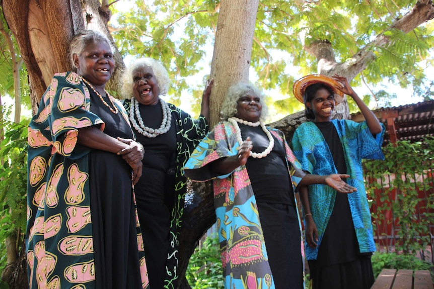 Four Aboriginal women wearing brightly-coloured fabrics and laughing.