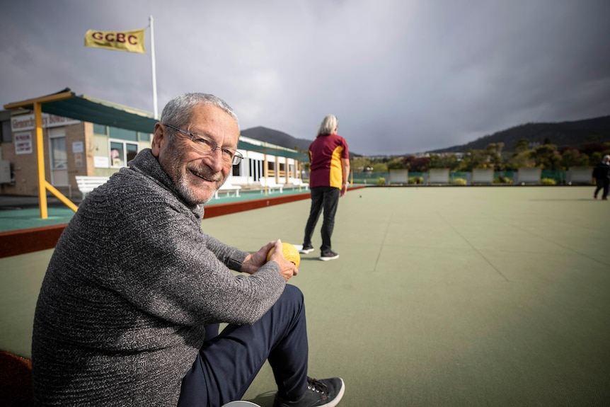 A man in a grey jumper with glasses with a woman on a lawn bowls green in the background.