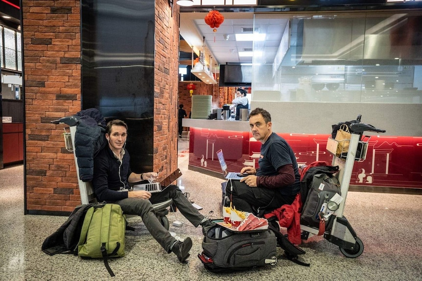 Two men sitting on trolleys in an airport on laptops