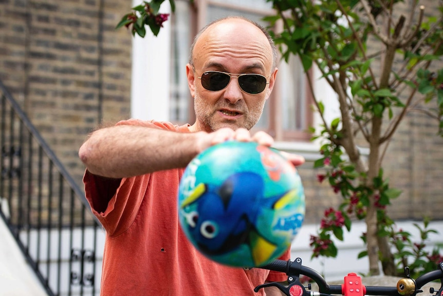 Unshaven , wearing a red t-shirt and sunglass, Dominic Cummings with a Finding Nemo balloon tied to a bicycle.