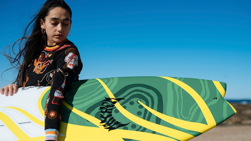 Woman holding a surfboard with indigenous designs