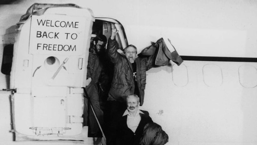 An old photo of smiling men disembarking from a plane
