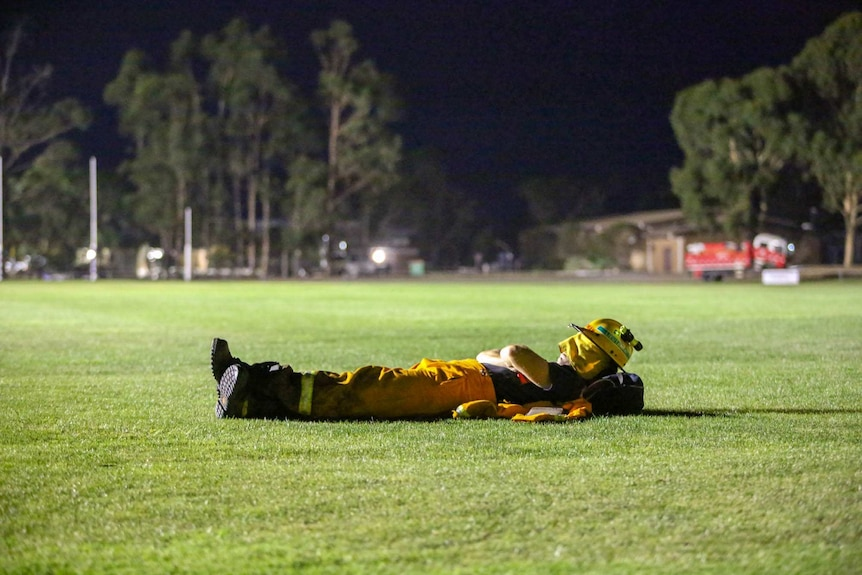 CFA volunteer sleeps on the oval at the Nar Nar Goon staging area