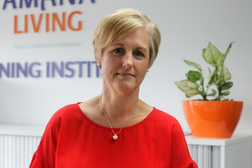 A midshot of a woman wearing a red top, with short blonde hair, stands in front of a white bench and a plant in an orange pot.