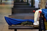 A homeless person lies on a seat on Adelaide Street in the Brisbane CBD.