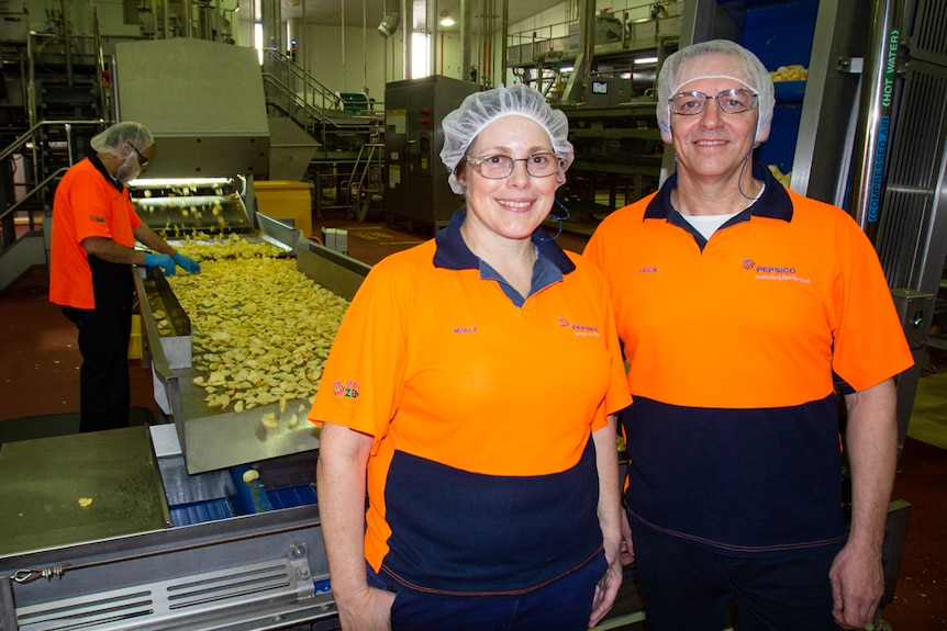 Woman and man standing in front of potato chip factory production line.