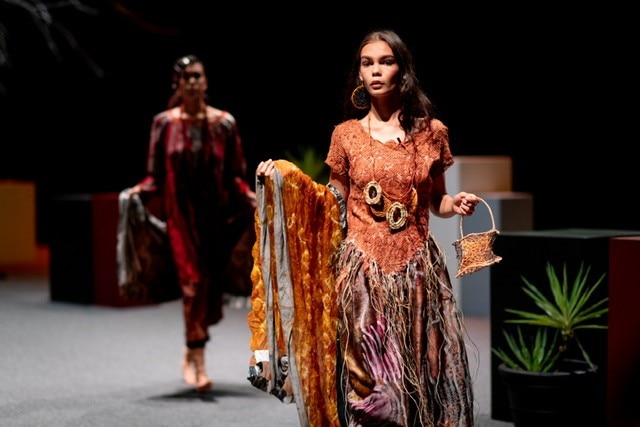A woman in First Nations fashion walks down a catwalk.
