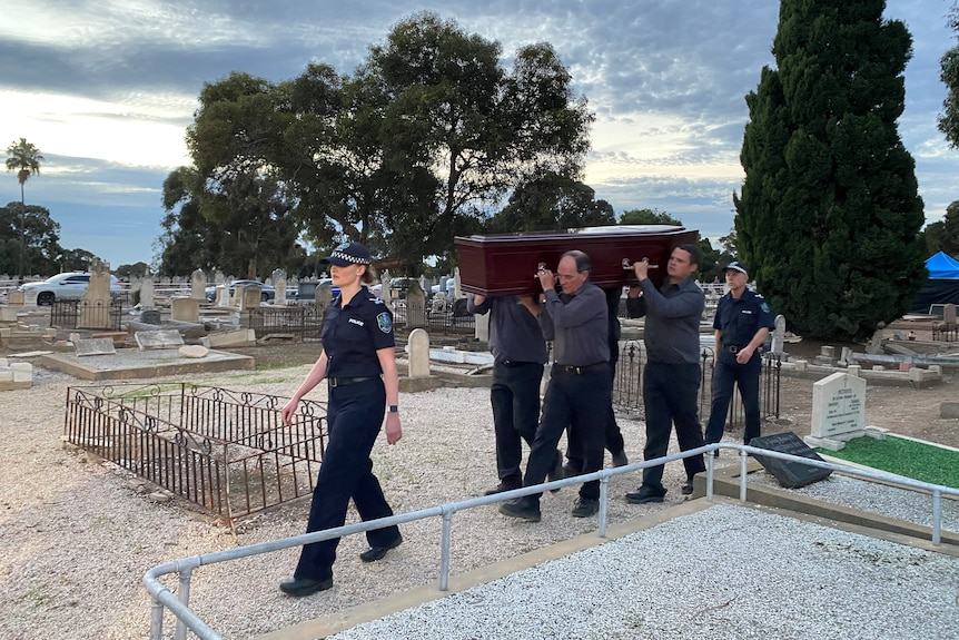 SA Police officers escort a coffin in a cemetery.