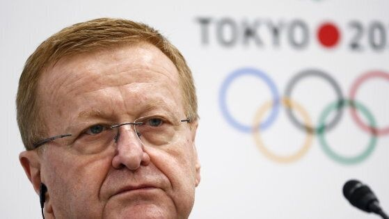 John Coates sits in front of a Tokyo 2020 Olympic logo sign at a media conference.