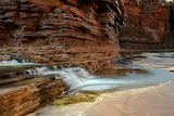 A close of the Karijini gorge and the water running through.