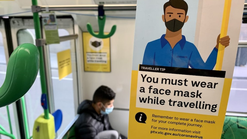 A sign reads 'You must wear a face mask while travelling' on the inside of a tram.
