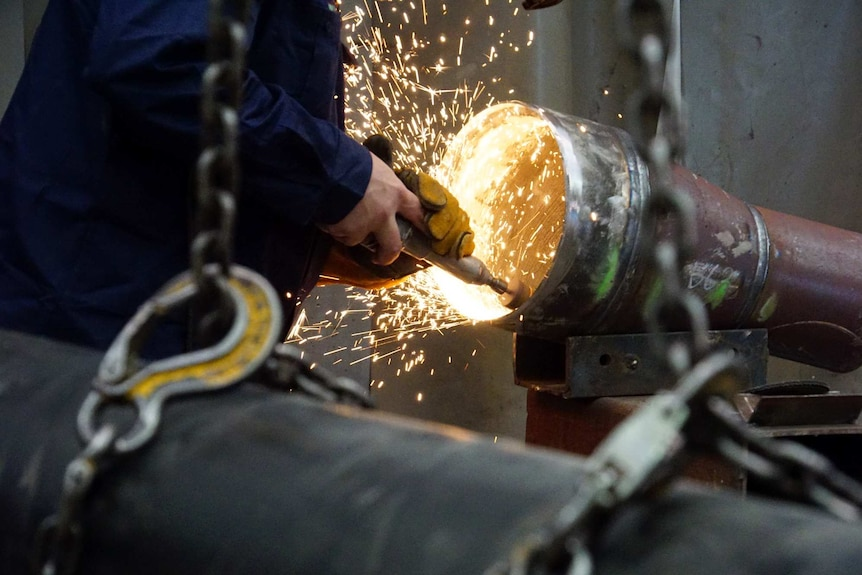 Worker grinds the inside of a pipe at Alltype Engineering, Perth, July 2016