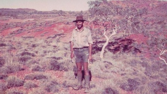 Jean-Paul Turcaud, wearing a hat, shorts, boots and big smile standing in desert by scrubby tree.
