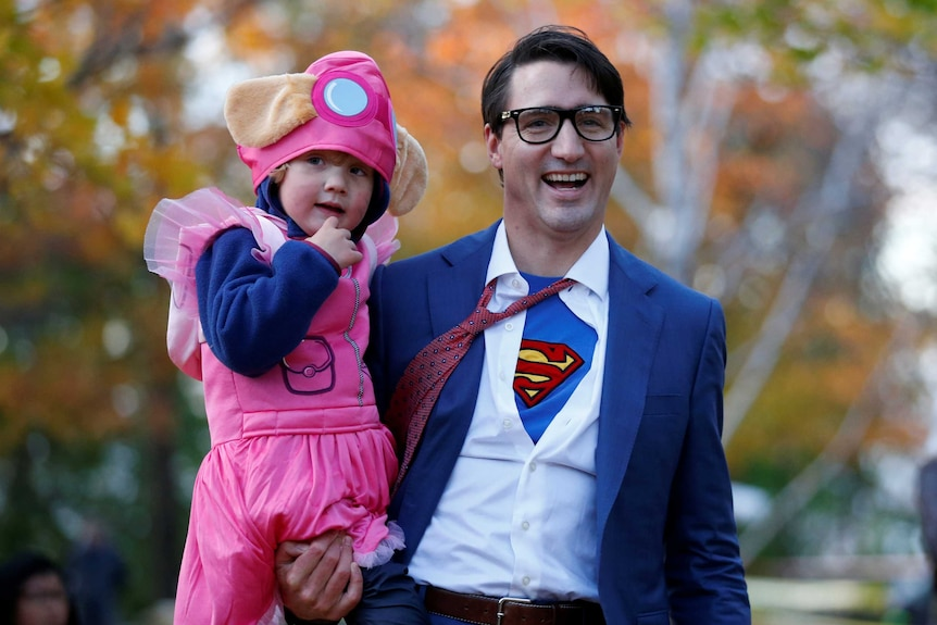 Canada's Prime Minister Justin Trudeau carries his son Hadrien while participating in Halloween festivities
