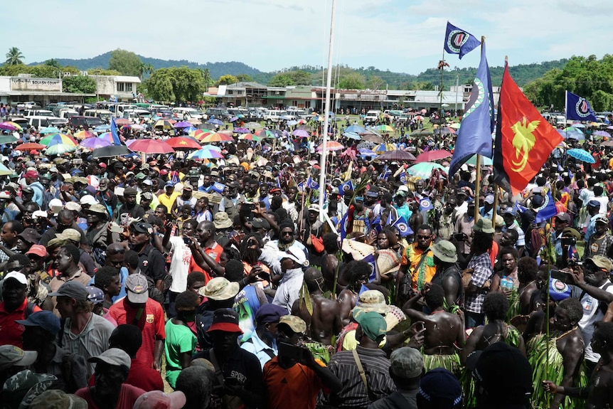 a large crowd of people gather in an open space with some holding flags.