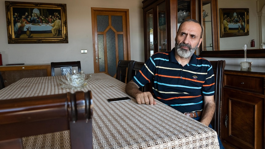 A middle-aged bearded Lebanese man in a polo shirt sits at a dining room table