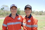 two young women in high vis shirts stand in front of a rail line