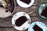 Four slices of chocolate olive oil on plates next to cut cake topped with pistachios and coconut.