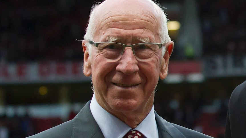 Bobby Charlton smiles at the camera wearing a grey suit with a red and white tie