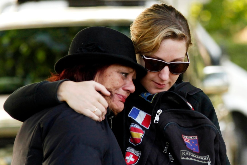 Two women hug at a memorial service to mark the first anniversary of the Christchurch earthquake.