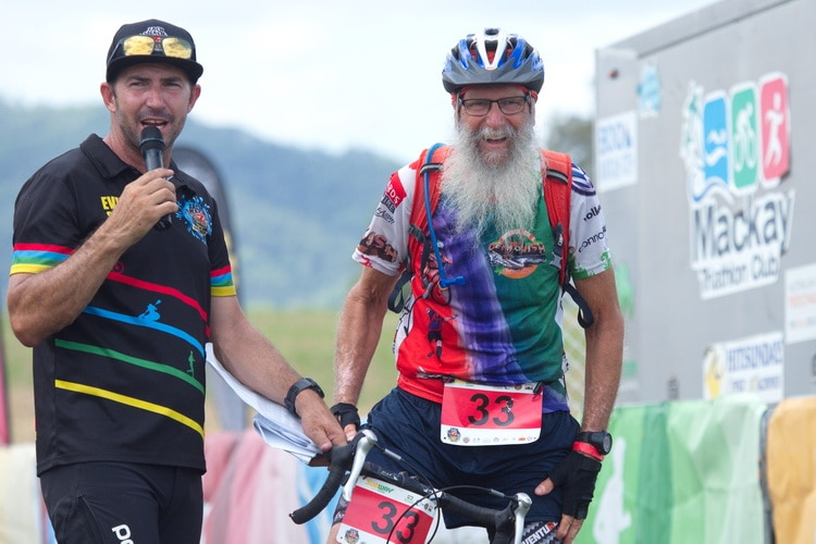 Two men at the finishing line of an event, one on a bike and one with a microphone.