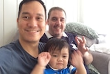 Two men smiling while holding their son.