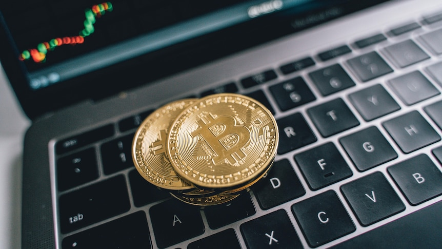 Three coins with the Bitcoin symbol sit on a laptop keyboard.