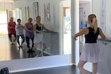 Mirror reflection of four senior ladies using bar to practice ballet poses
