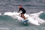 A surfer wearing a Christmas hat rides a wave on his surfboard on Christmas Day at Sydney's Bondi Beach